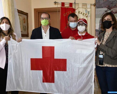 La bandiera con l'emblema della Croce Rossa Italiana sventola sul palazzo municipale in Piazza XIX Maggio.